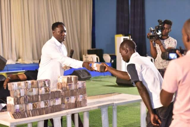 Pastor distributes bundles of money to church members to celebrate Christmas