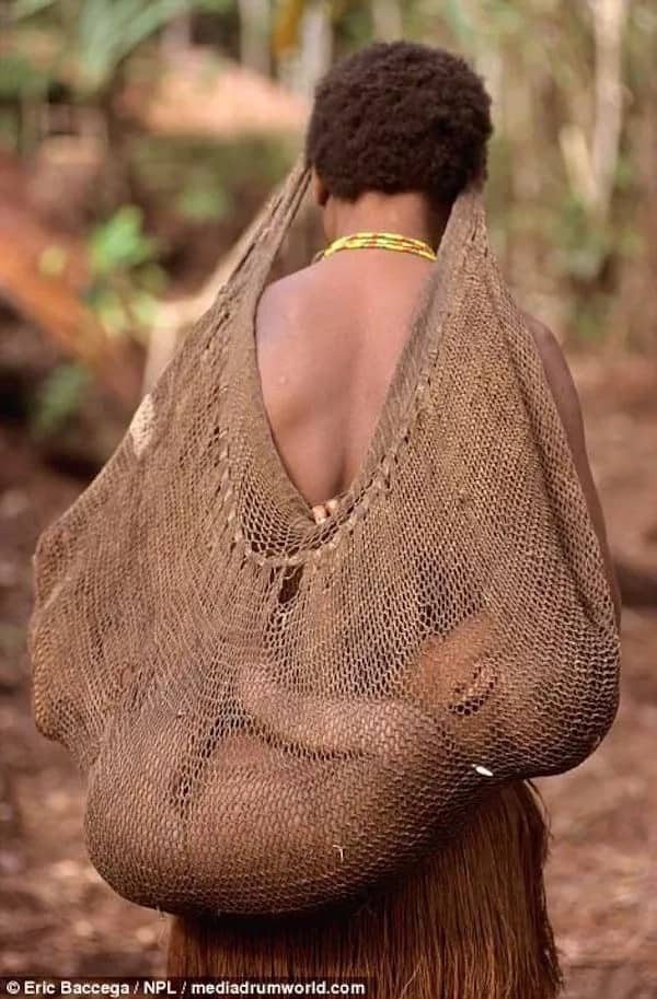 A Korowai tribeswoman carrying a baby on her back. Photo: Eric Baccega