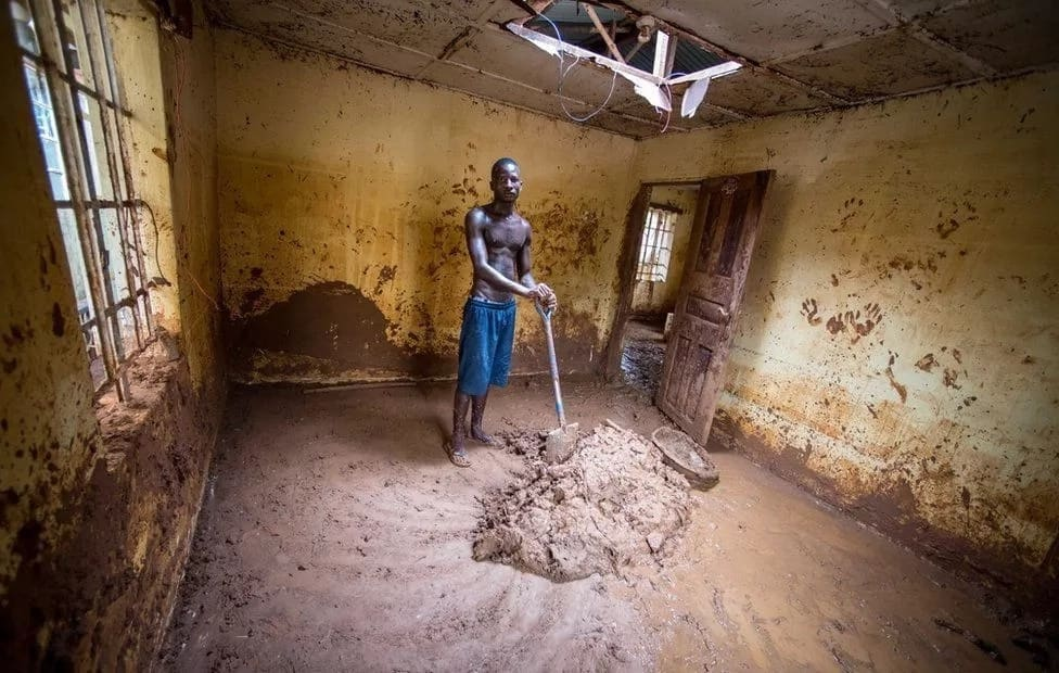 Abdul Mansaray gathers the mud in his house. Photo: BBC