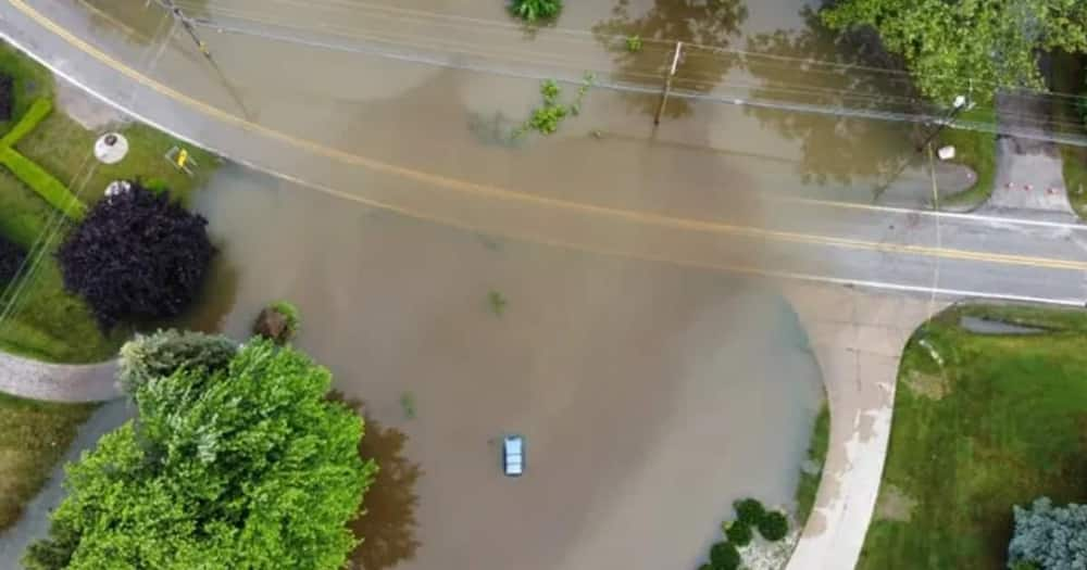 The woman was trapped inside her car which was in the middle of the flooding waters.