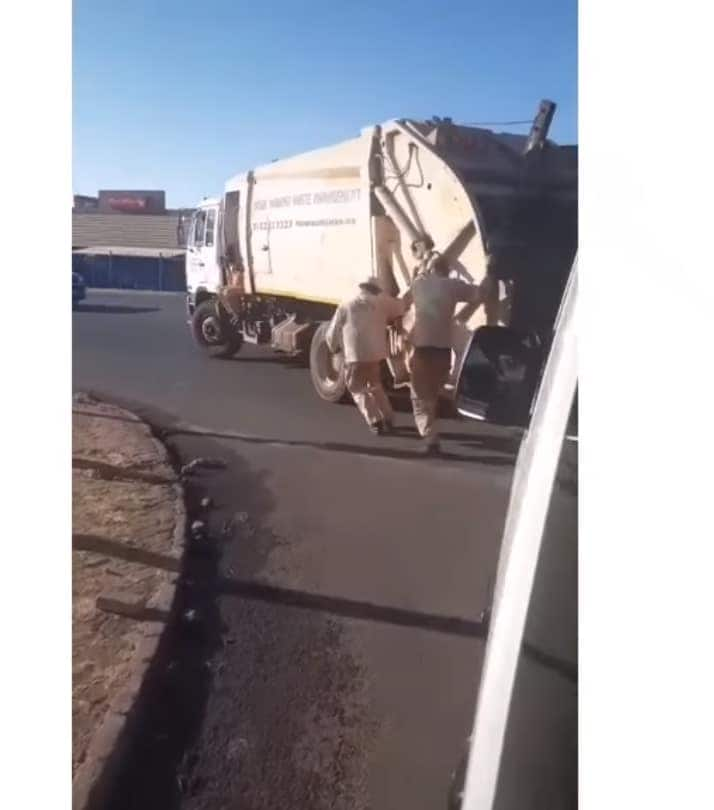 Two waste pickers dance to the music playing the car behind them