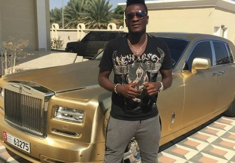 Asamoah Gyan poses with his fleet of cars from his mansion