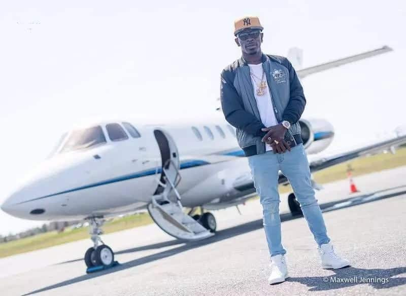 Shatta Wale stands in front of a private jet