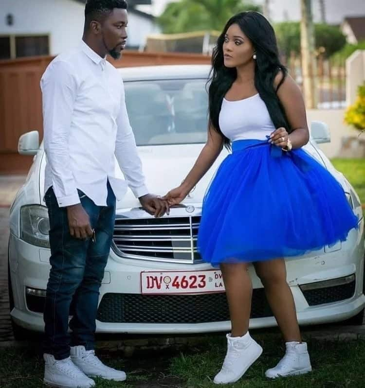 Ghanaian couple hold hands standing in front of a car
