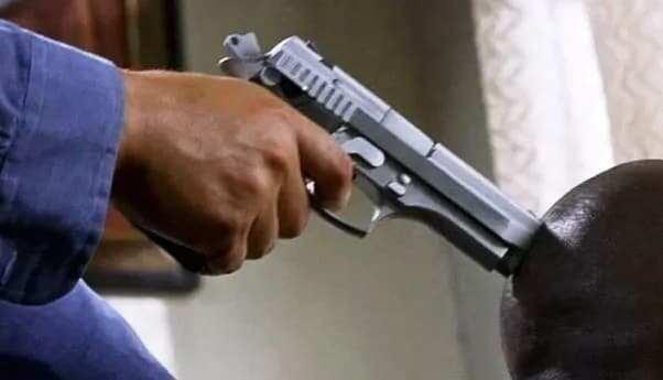A gun pointed to a head