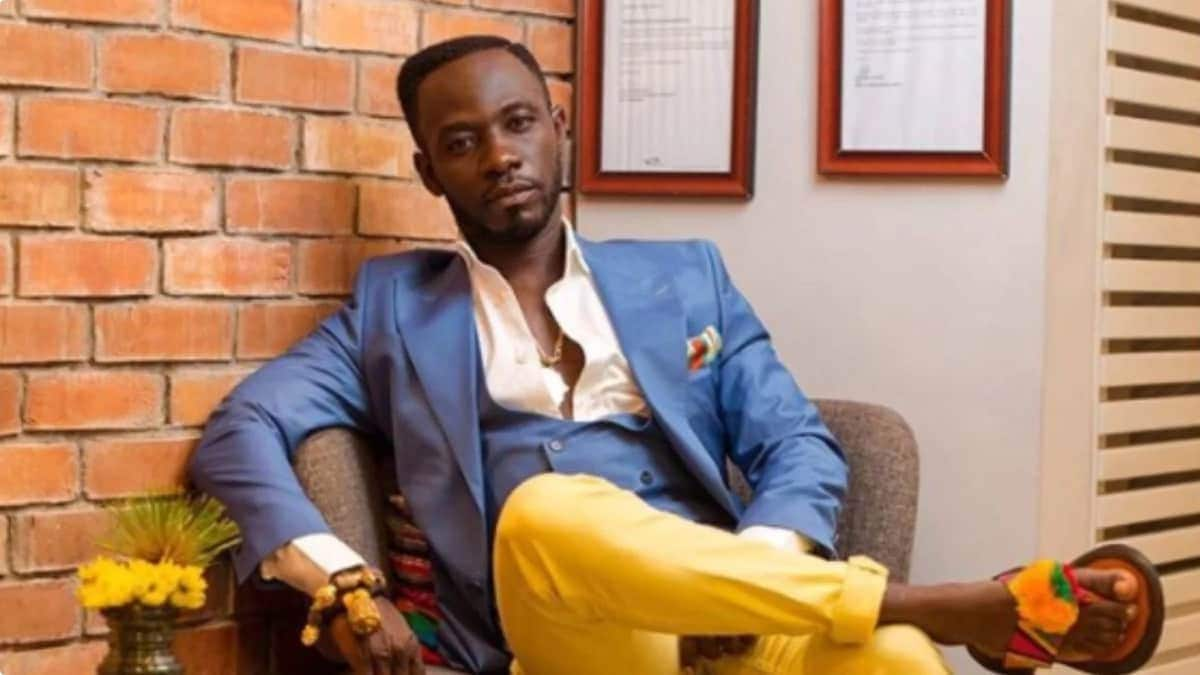 Okyeame Kwame sits down in blue blazer and Kente slippers
