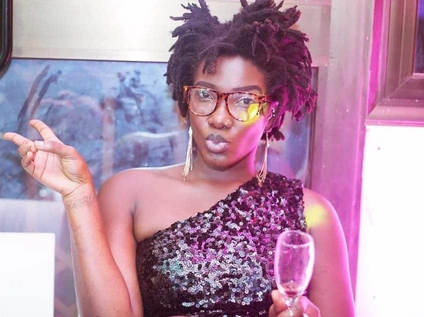 Ebony holding a glass of wine