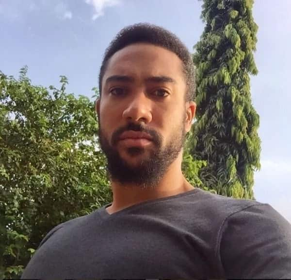 Majid Michel in a grey shirt starring downwards into a camera