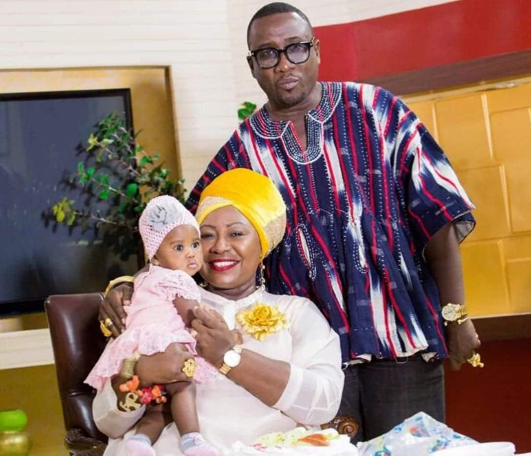 Gifty Anti sits with her baby as her husband stands behind her
