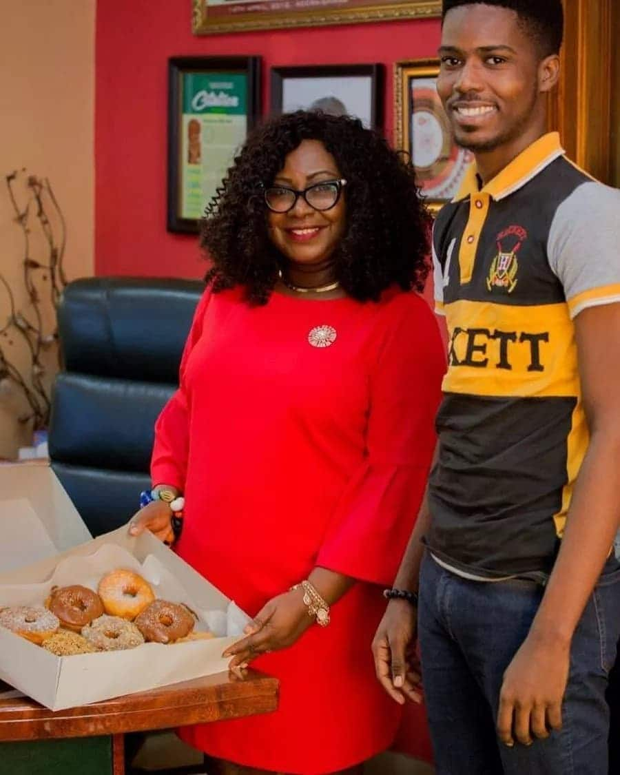 Gifty Anti opens a box of doughnuts with a man beside her