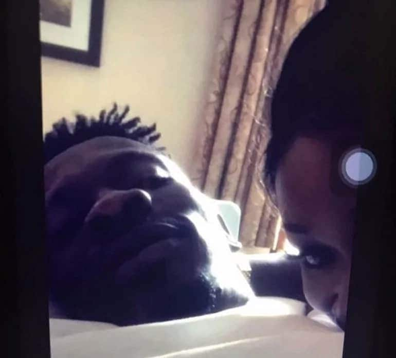 Shatta Wale lying on a bed