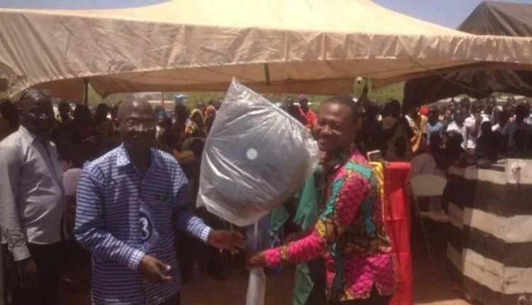 A teacher receiving a standing fan as a prize