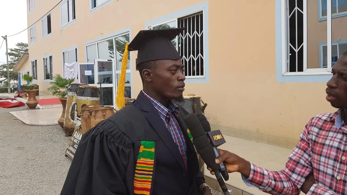 Lilwin in matriculation gown speaking to the press