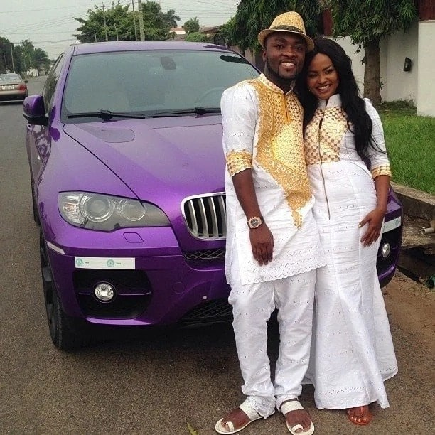 Nana Ama McBrown and her husband standing in front of a car