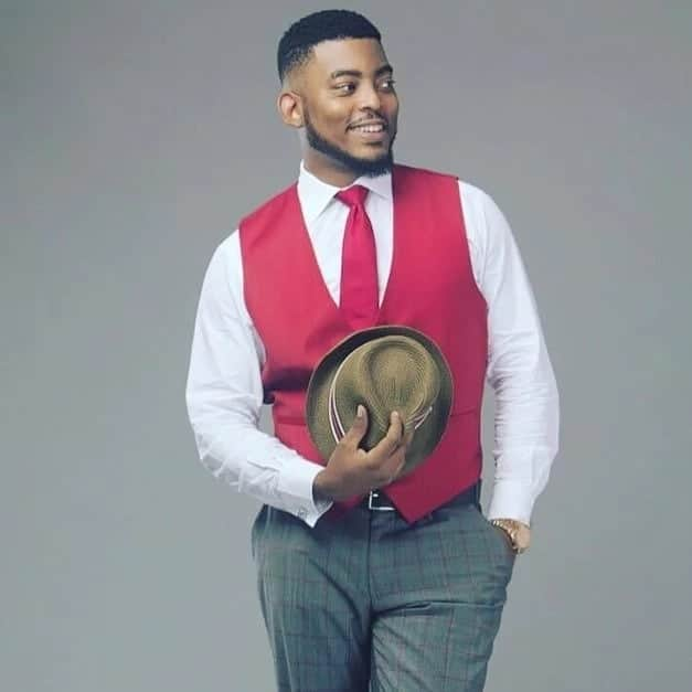 Ghanaian actor holding a Fedora hat