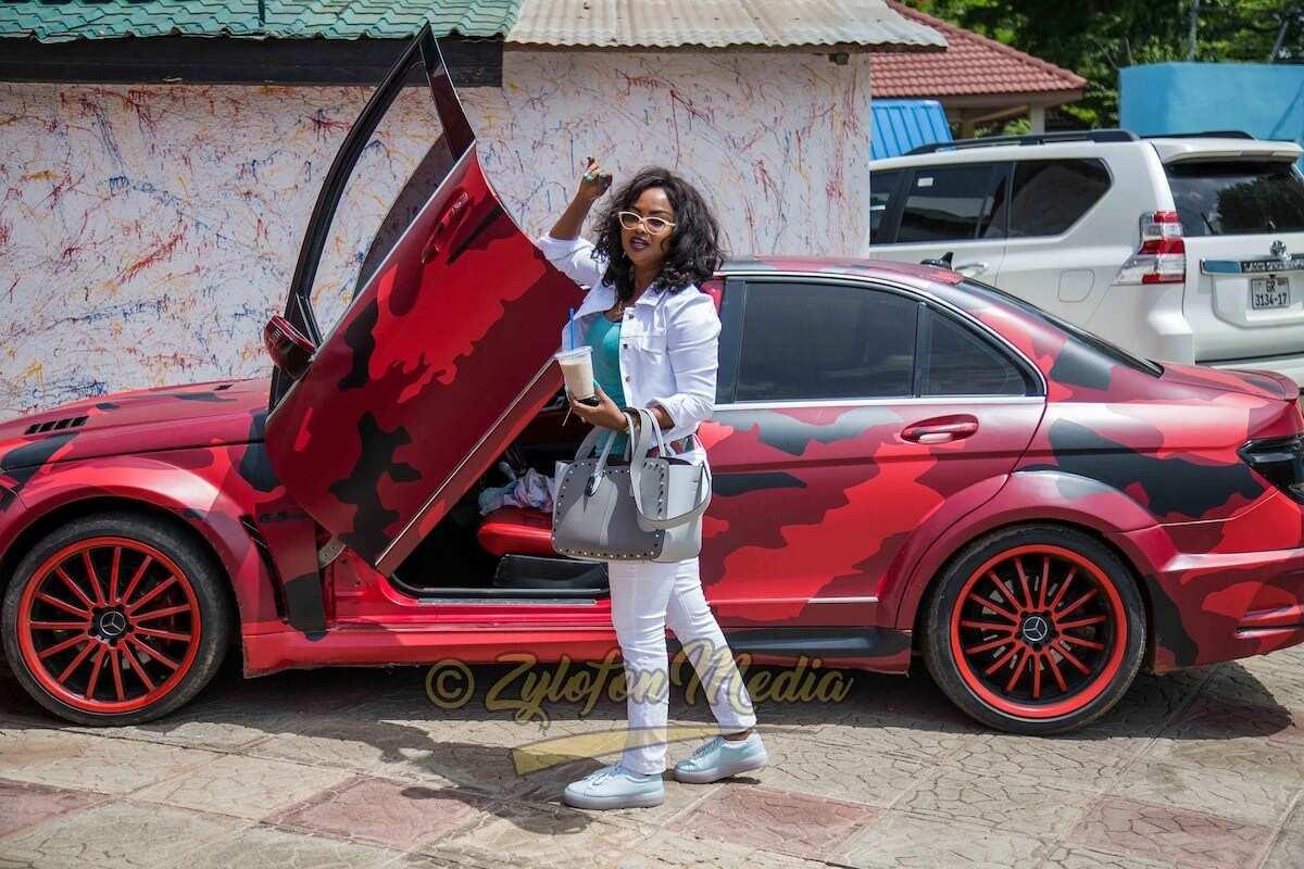 Nana Ama McBrown standing beside her BMW