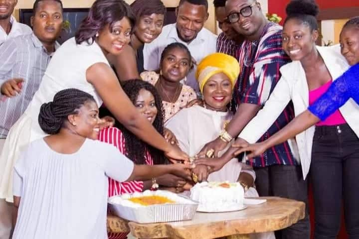 Gifty Anti cuts her cake with a group of people