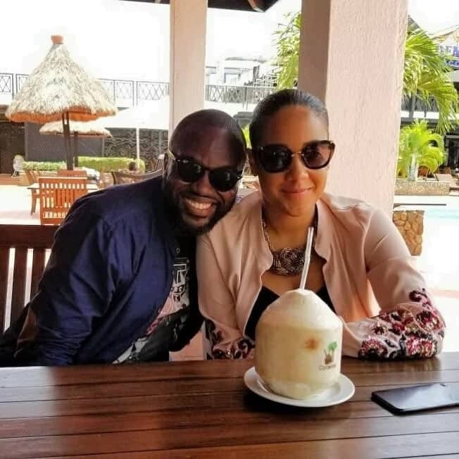 Happy Ghanaian couple with a coconut in front of them