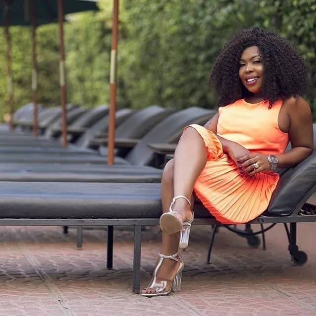 Afia Schwa seated with her legs crossed