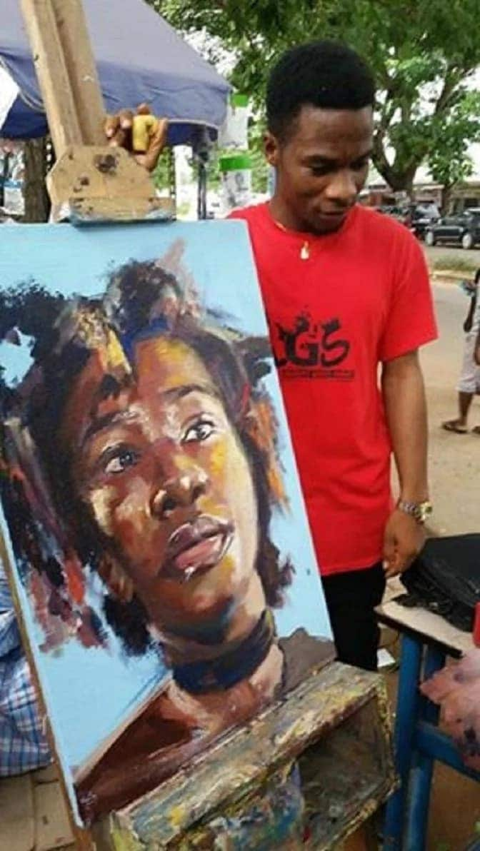 An artiste standing behind a painting