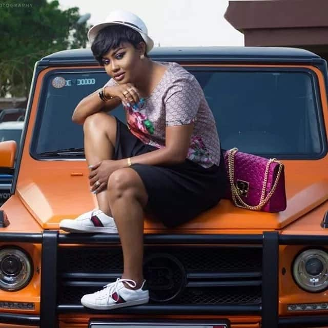 Nana Ama McBrown seated on the bonnet of a car