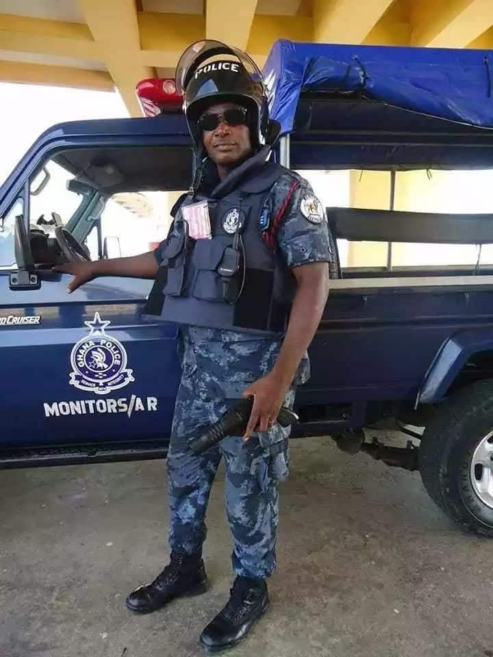 Ghanaian police officer stands next to a police vehicle