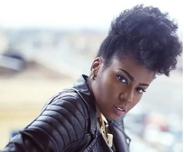 MzVee wearing a leather jacket with an Afro hairstyle
