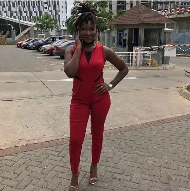 Ebony Reigns in red jumpsuit smiling