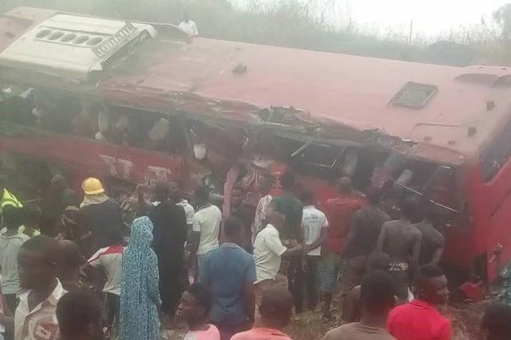 People surrounding an overturned bus