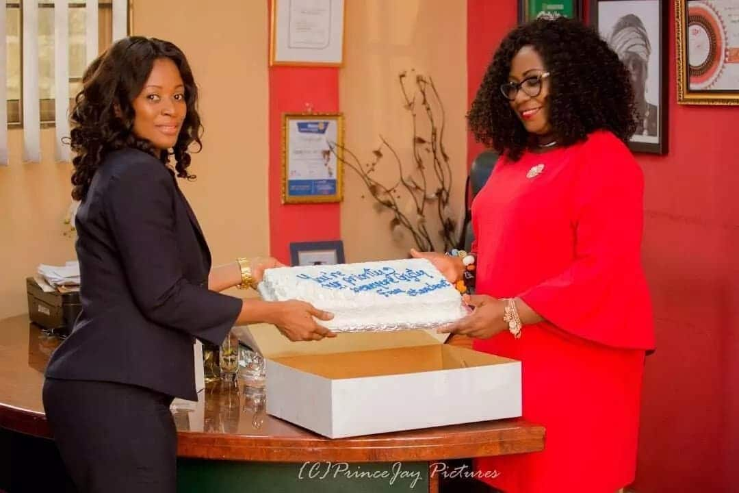 Gifty Anti receives a cake from a woman
