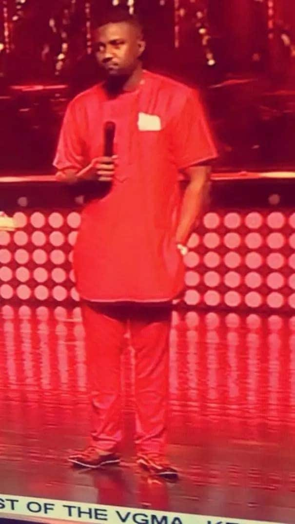 John Dumelo wearing a red outfit