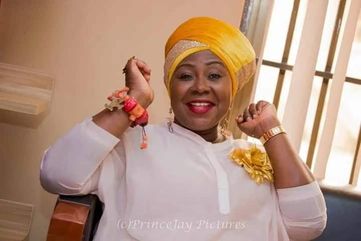 Gifty Anti in a yellow turban and white shirt similing