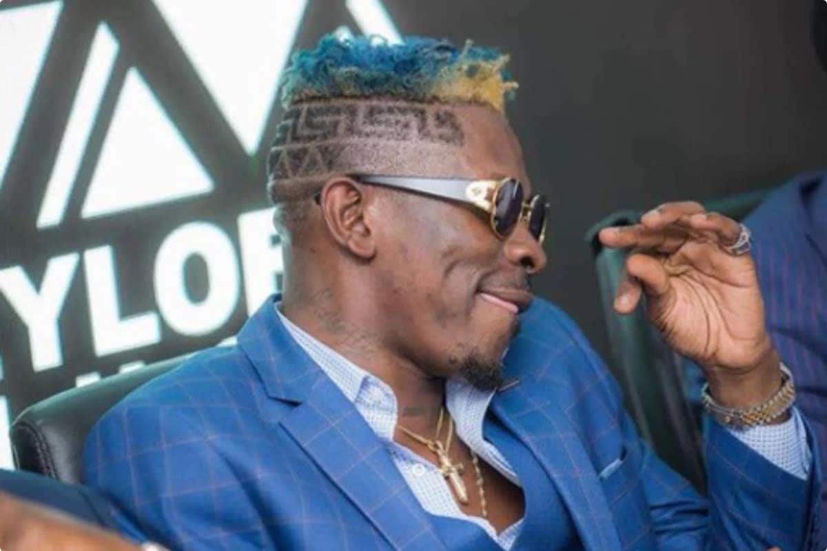 Shatta Wale in blue jacket with blue and yellow hair