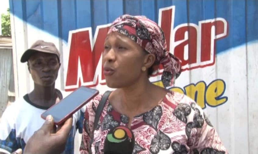 A woman speaking to journalists