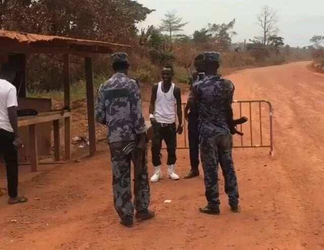 Patapaa standing with three policemen