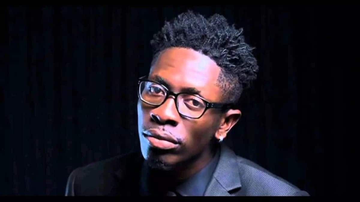 Shatta Wale in a black suit and spectacles