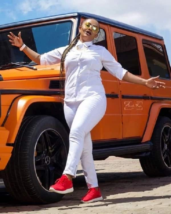 Nana Ama McBrown in a white outfit and red shoes standing in front of an orange jeep