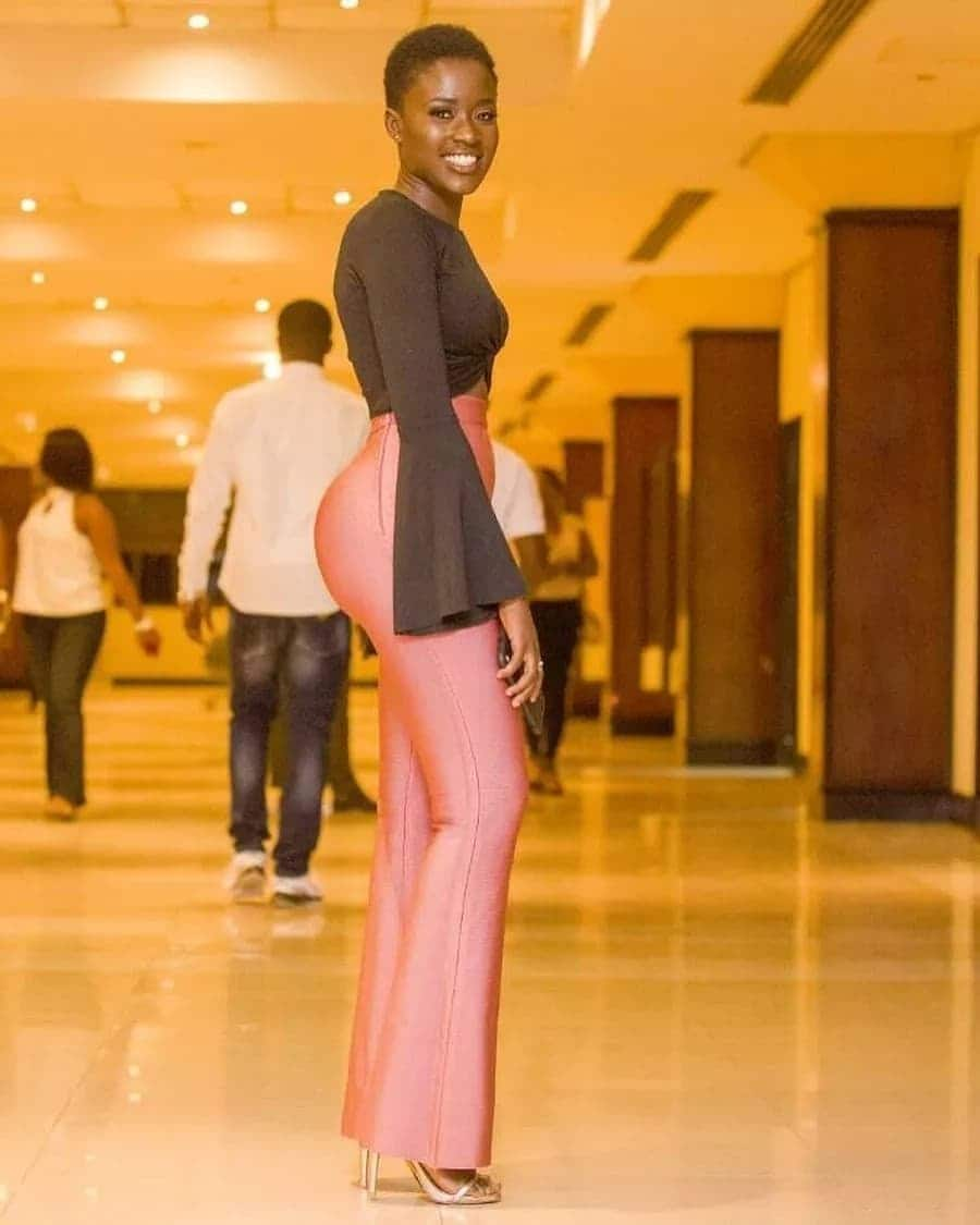 Fella Makafui in a black top and pink trousers