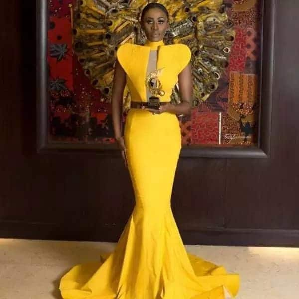 Ghanaian actress wears yellow gown and holds award plaque