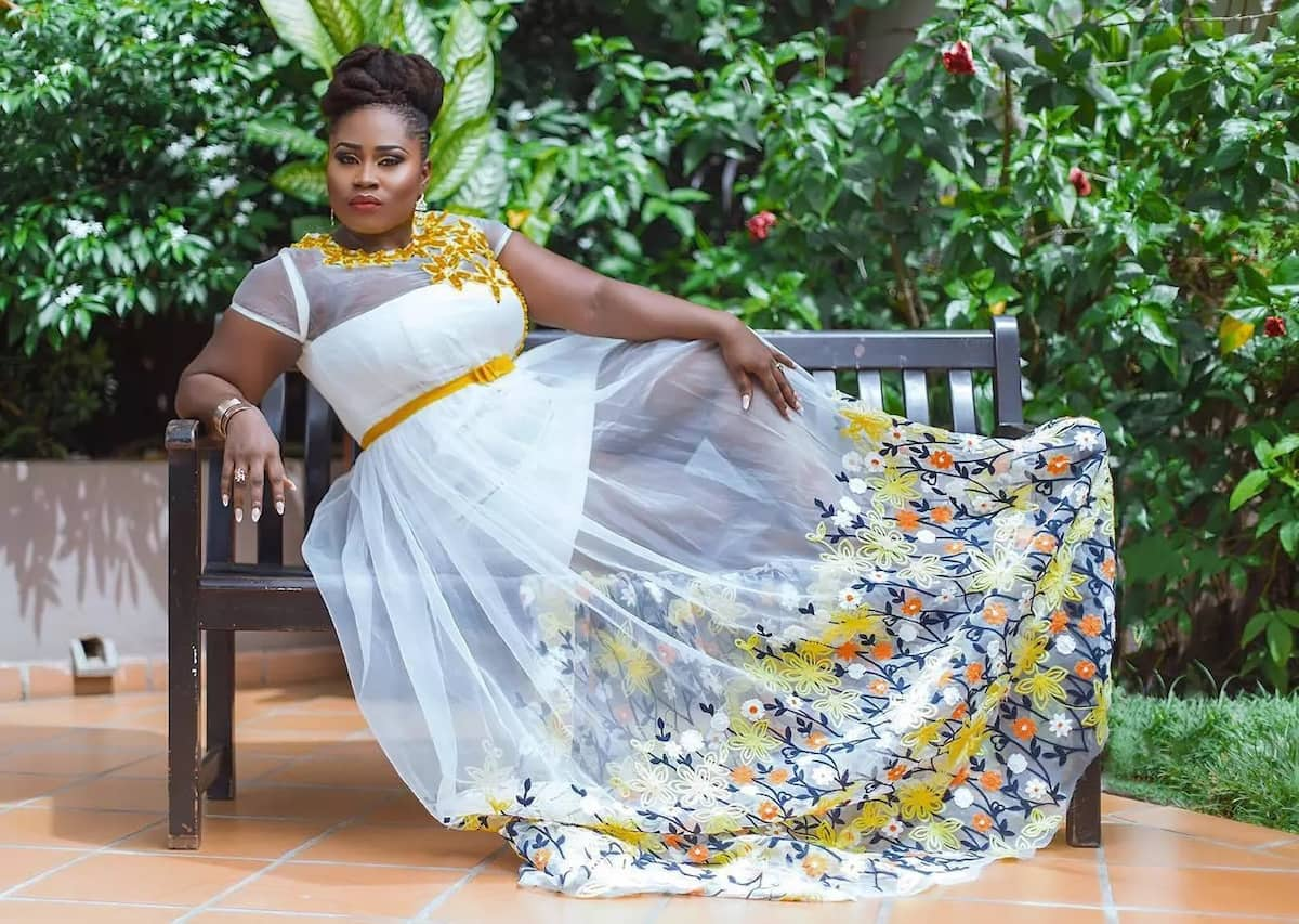 Lydia Forson sits on wooden bench in flower patterned dress