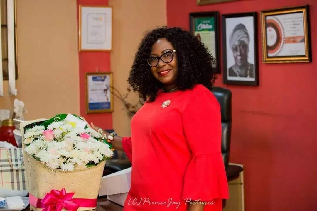 Gifty Anti in a red dress with a flower bouquet