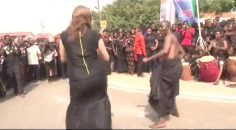 Man and woman in black traditional funeral cloth, dancing