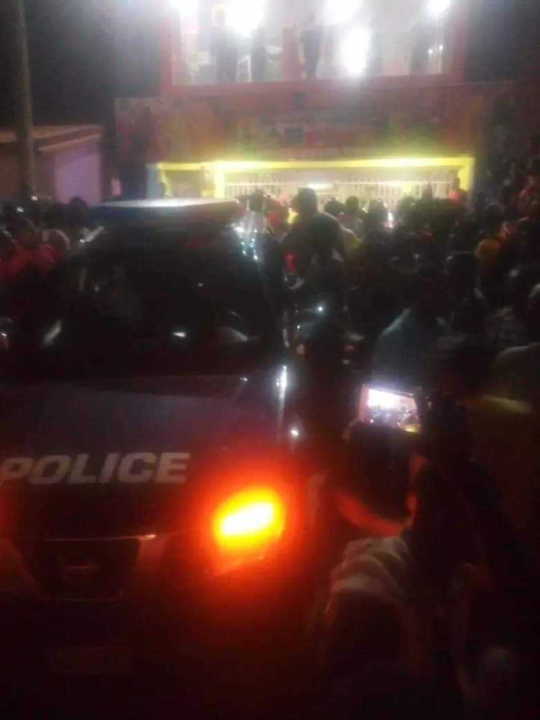 People gathered around a police vehicle