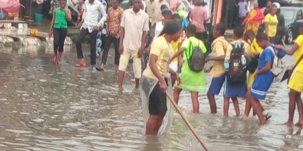 Nigerian Lady Goes Under The Rain To Help School Children Cross A Flooded Market