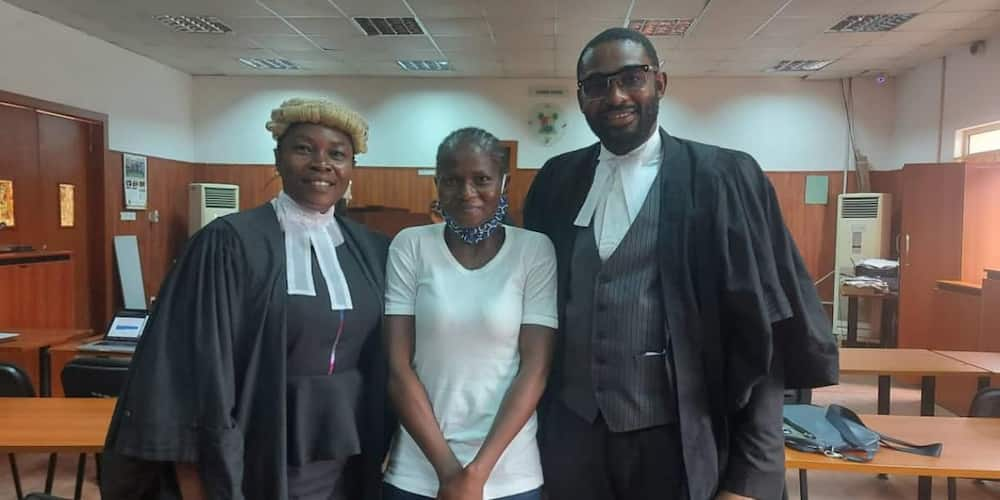 Titilayo Benson flanked by two lawyers