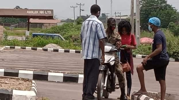 The picture showing the lady as she was about to mount the soldier's bike. Photo source: The Cable